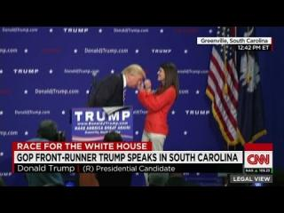 Woman inspects Donald Trump''s hair on stage